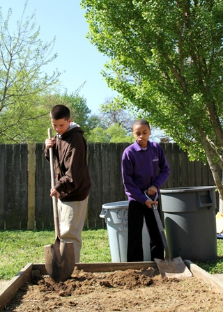 Volunteers from Barret Traditional Middle School get the garden ready for planting